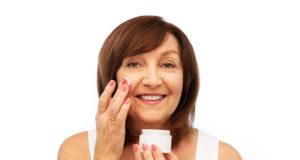 Dojrzała kobieta pielęgnująca twarz kremem przeciwzmarszczkowym